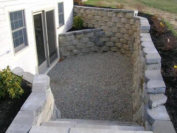Create A Walkout Basement With Use Of Retaining Walls And A Clever Walkway And Stone Steps This Will Ligh Basement Remodeling Basement Windows Basement Design