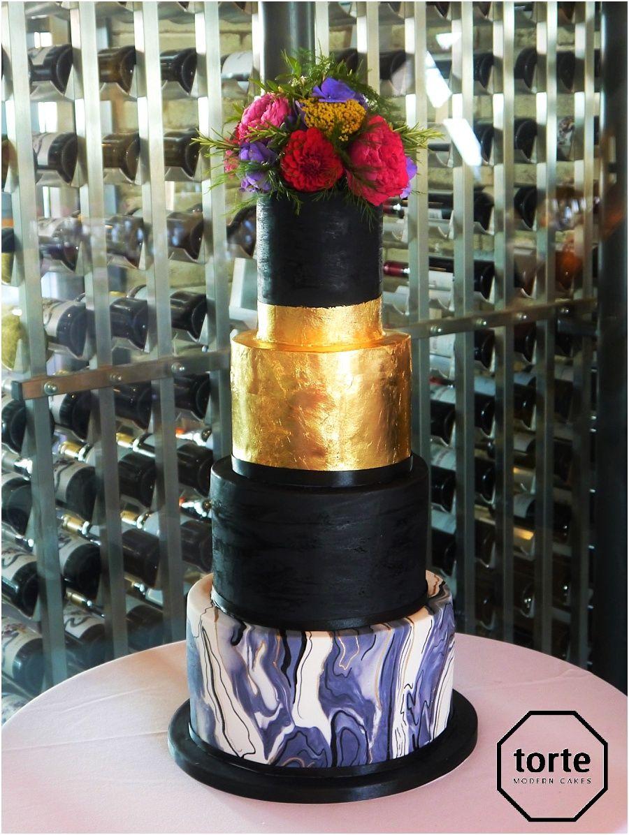 Black u gold marble wedding cake with gold leaf and fresh flowers