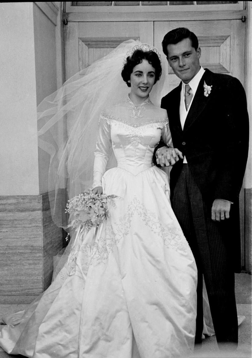 Actress Elizabeth Taylor is wearing a beautiful long satin wedding ...