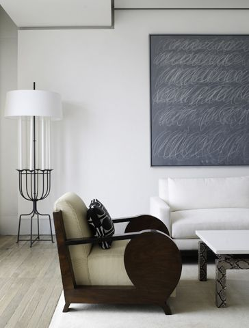 A Cy Twombly painting anchors the living and dining room. A 1930 Dominique Studio Art Deco chair, Tommi Parzinger floor lamp and custom sofa and python-base coffee table grace Burke's restrained composition.
