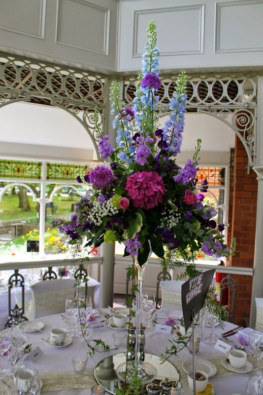 Tall elegant Martini Vase designs with fabulous Delphiniums towering over the Alliums, Peonies, Roses and Hydrangeas