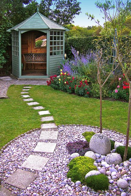 garden designed with pebble pattern stone path through a pebble circle bed and lawn pebble circle planted with seaside plants pretty gazebo at the far - Garden Design Circles