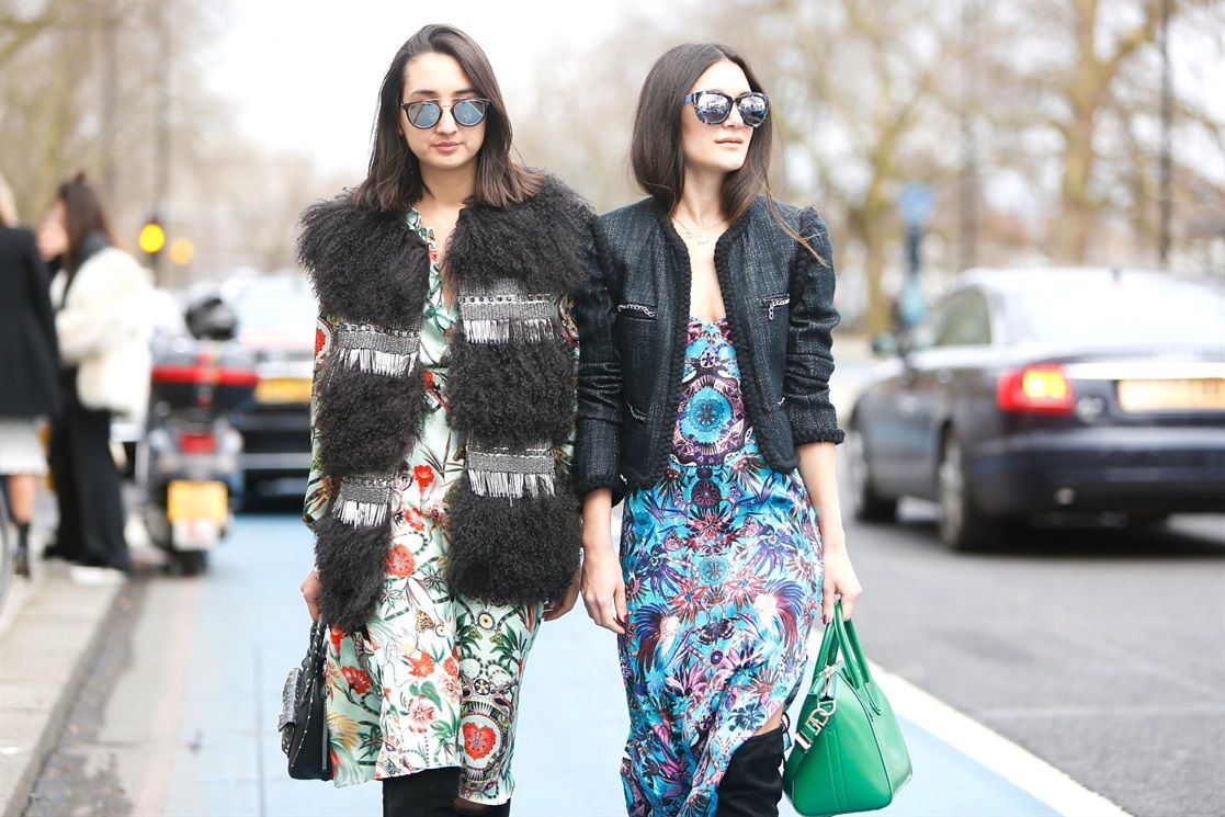 Fashion blogger Anisa Sojka and Gabriela tones spotted during London Fashion Week. Gabriela wears the Matthew Williamson mother amazon mint shirt, midi skirt and fur gilet. Anisa wears the blue printed slip dress with a cropped jacket and green Givenchy handbag - Street Style via Vogue Italia