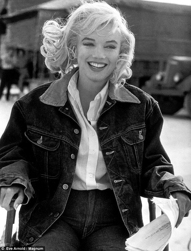 At ease: A relaxed and happy Marilyn, dressed down in denim, reads the script on set of her last completed film