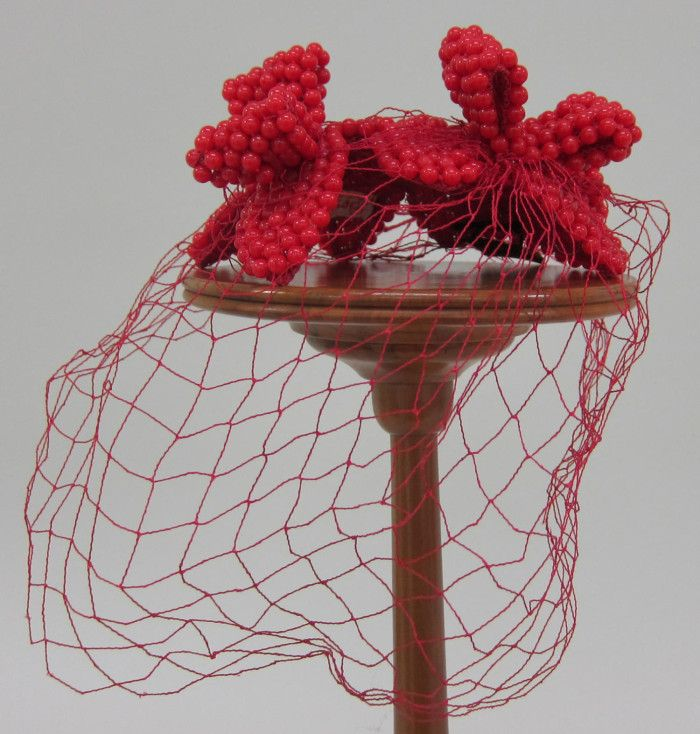 Hatlet with red net veil | Designer: Benjamin B. Green-Field (Bes-Ben) | United States, 1970 | Crown of the hatlet is composed of an irregular skullcap of stiffened red mesh covered with red beads | Set atop the the hatlet are three large 'bow' shapes composed of the red beads | University of North Texas