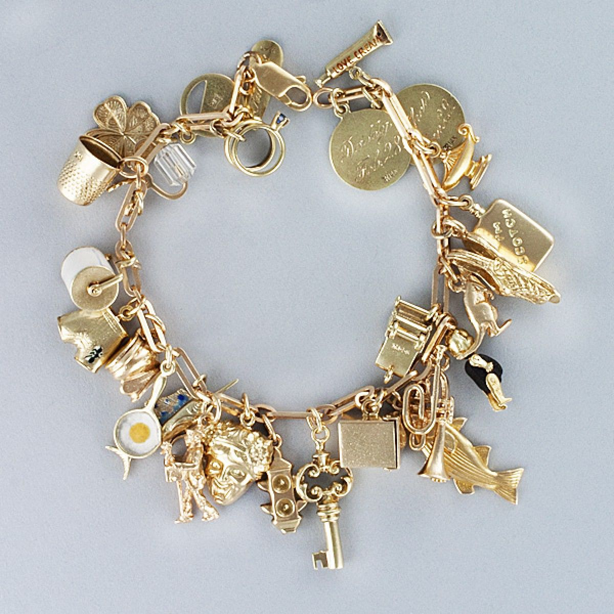 Assorted charm bracelet in 14k yellow gold. Length 7.5 inches...