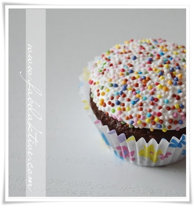 {Fabelaktig} cupcake with marshmallow frosting and sprinkle.