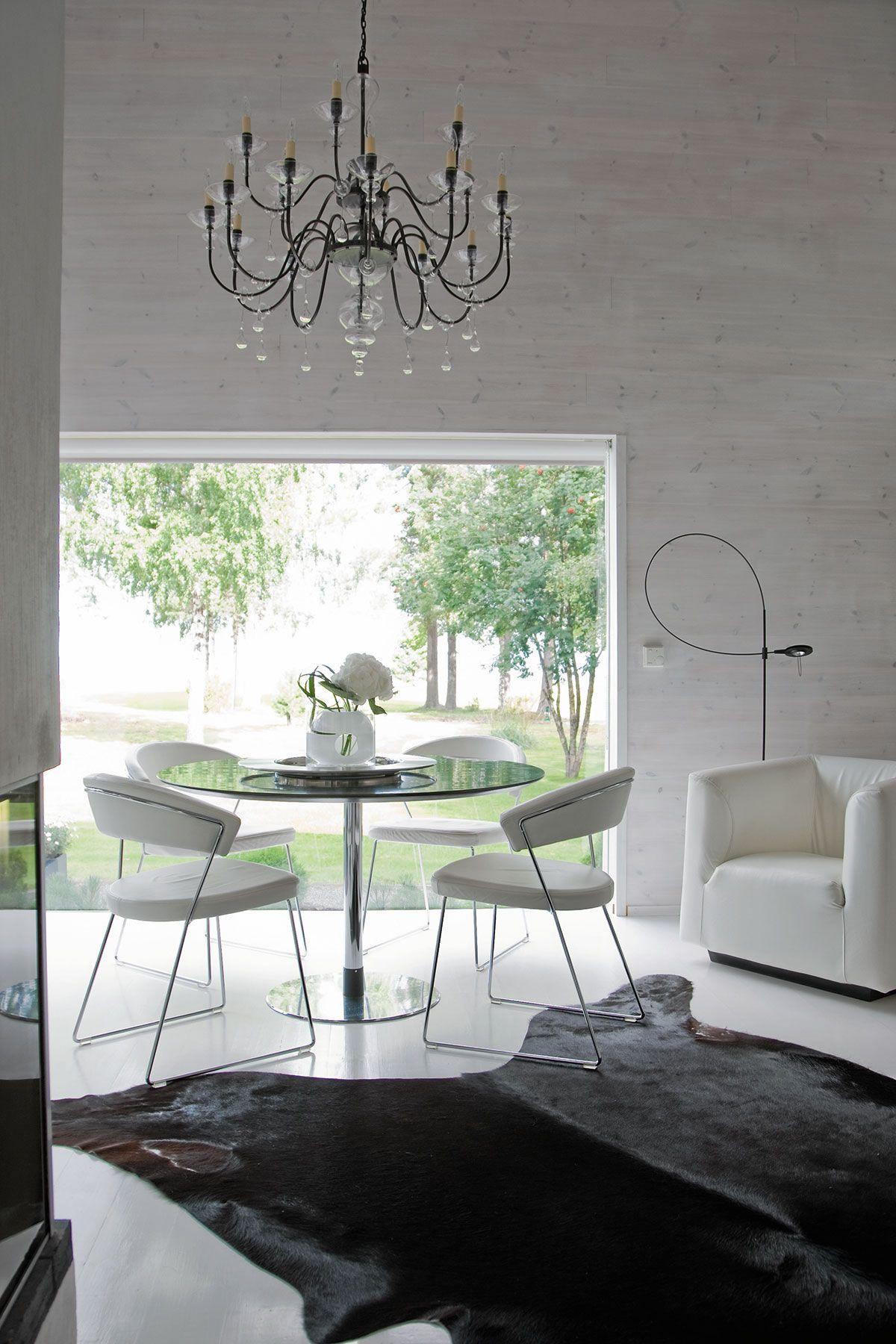 Musta ruokapöytä on Kuokkasten ensimmäisestä kodista vuodelta 1970. Sen ympärille hankittiin kakkoskotiin Calligarisin tuolit. Koristeellinen kynttelikkö lisää ripauksen huumoria kurinalaiseen modernismiin.