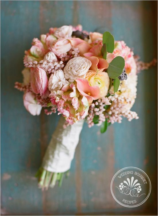 A beautiful soft pink bouquet filled with ranunculus, hydrangea, dutch tulip, calla lily, balsa wood, lotus pod, peiris, and eucalyptus.