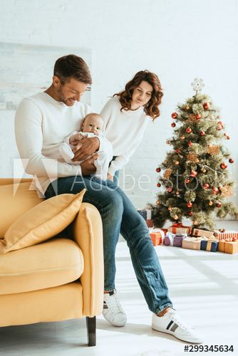 happy woman standing near christmas tree and looking at husband holding cute baby , #AFF, #standing, #christmas, #happy, #woman, #tree #Ad