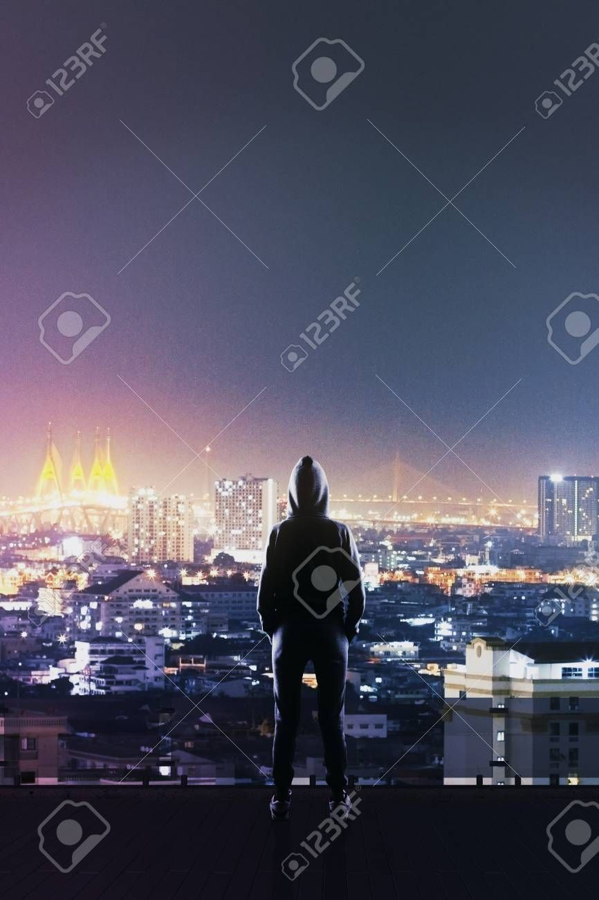 hackers back silhouette standing on roof top and looking at night megapolis city