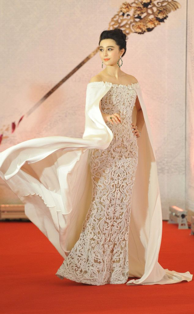 Fan Bingbing stuns on the red carpet in a white off shoulder embroidered lace Ralph & Russo gown with a long white cape. Dramatic and Exquisite! I love the movement of the cape!