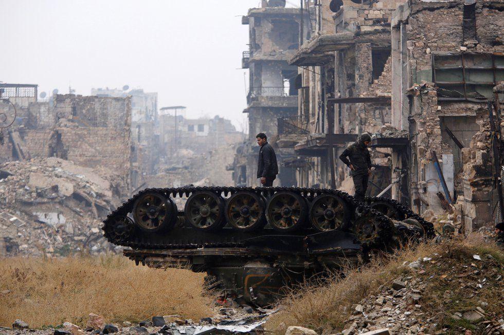 El Ejército sirio ya controla toda la ciudad de Alepo y ha detenido sus operaciones militares, aseguró el embajador ruso ante la ONU, Vitaly Churkin. En la imagen, fuerzas leales al presidente de Siria, Bachar el Asad, inspeccionan un tanque dañado, en Alepo.