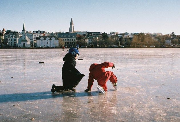 Kids playing on the frozen pond on a sunny winter day in Reykjavik, Iceland