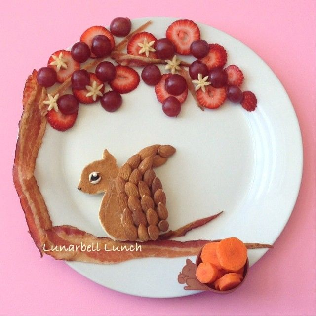 Squirrel lunch! I made the squirrel out of a PB&J sandwich with an almond tail! The tree is made with bacon, strawberries, grapes and bananas. In the cute squirrel food cup is a cut up carrot.