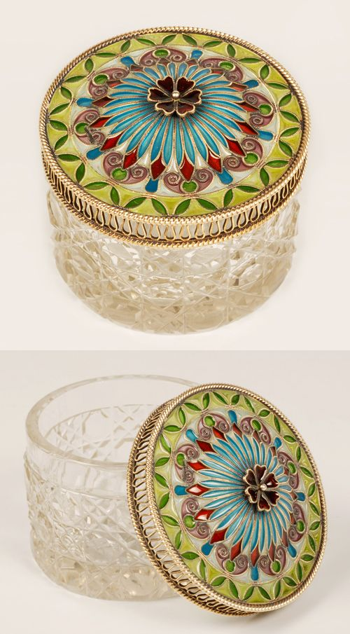 A Norwegian gilded silver and plique-a-jour eanmel lidded cryatal box, circa 1900. The round cut glass box is fitted with a lid of translucent enamel in shades of green, turquoise, red and violet enamel. The domed radiating ray desigh in turquoise is centered with a deep red six-petal enamel flower finial.