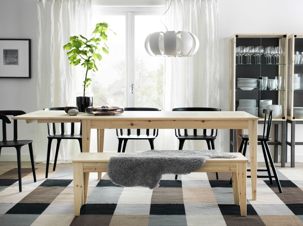 A dining room with a NORNS dining table in pine wood and IKEA PS