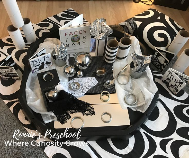 Black and White with a touch of reflective and silver materials for a beautiful and engaging Tuff Tray filled with loose parts for babies and toddlers. Simple play items for sensory play!