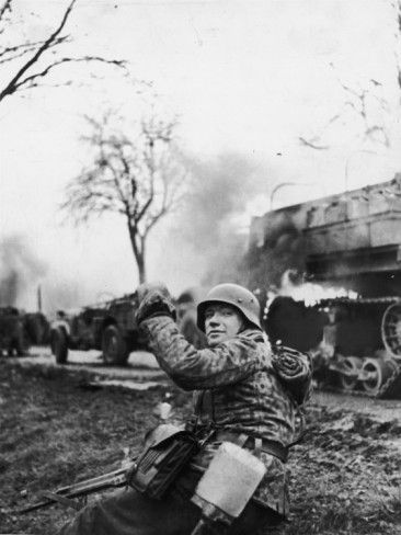 """German Soldier Urging Comrades Forward During the Battle of the Bulge - This is after the """"battle"""" or """"ambush"""" at Poteau.  KG Hansen intercepted a US cavalry screen and wiped it out.  For propaganda purposes the event was immediately re-enacted by the KG.  Then actual pictures of the aftermath and staged pictures like these were intermingled to make very realistic sequence of pictures."""