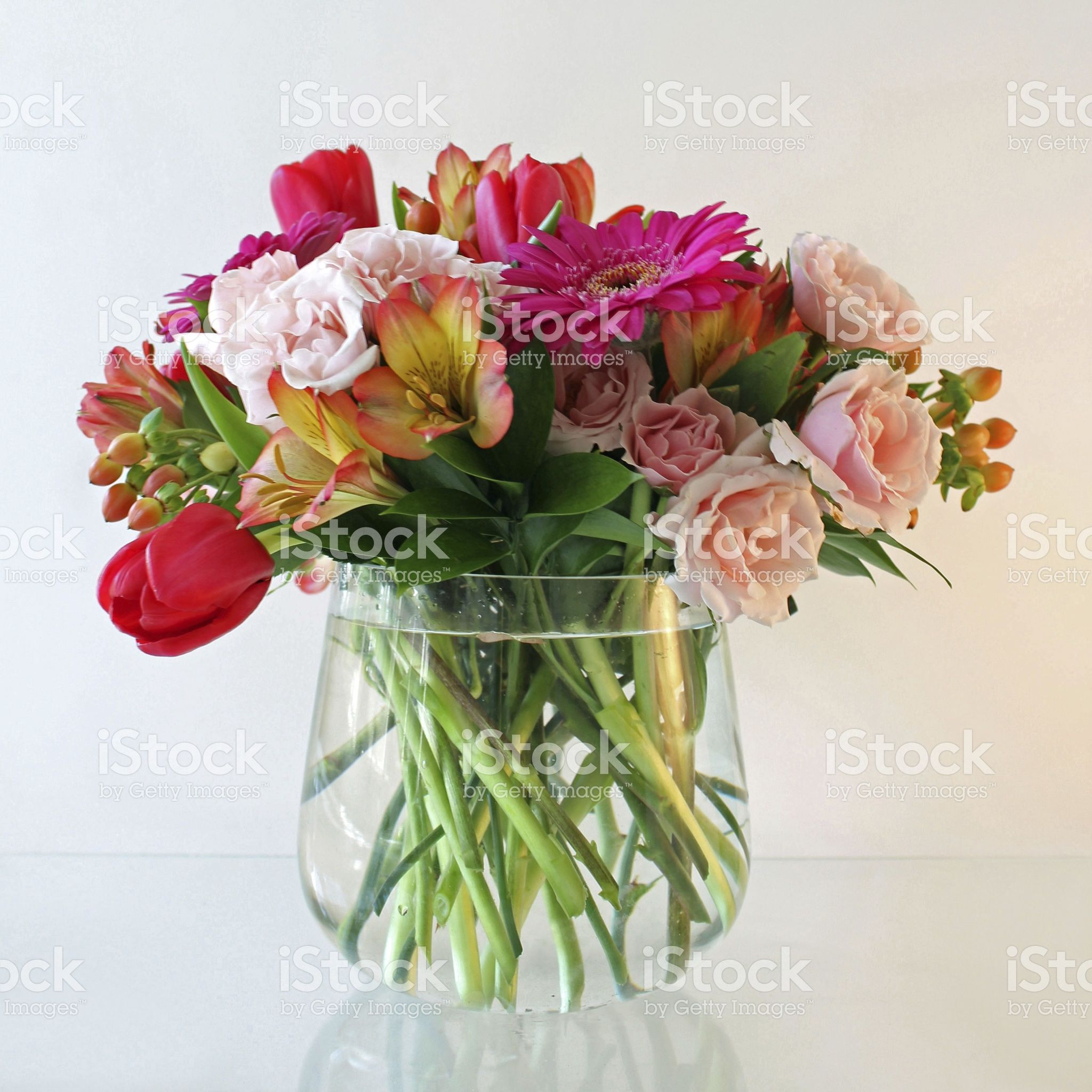 A Glass Vase With An Arrangement Of Pink Red And Orange Flowers