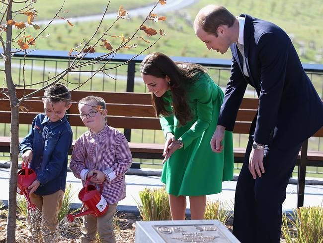 Kate and William watch two children help them with a tree planting. Picture: Getty Images