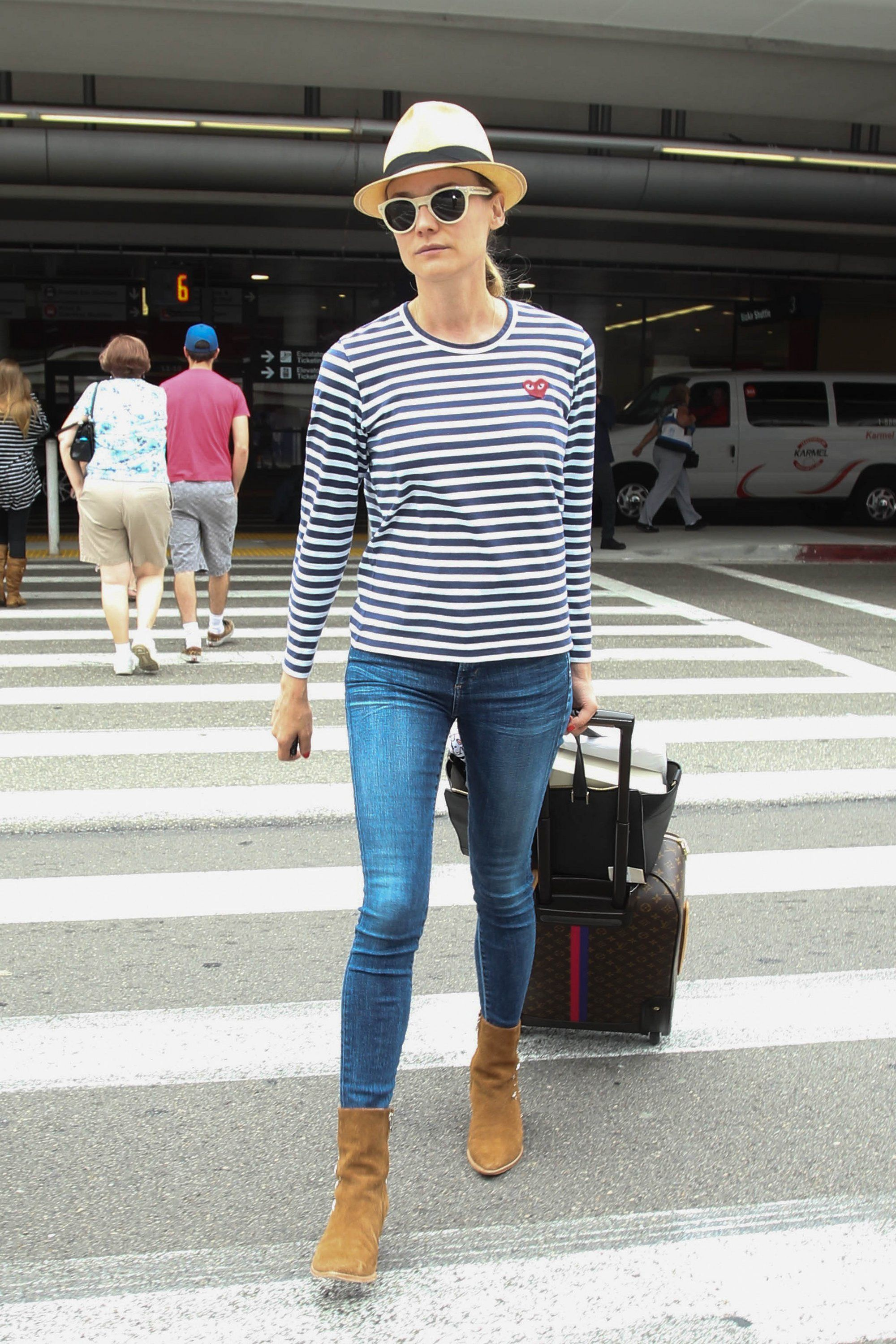 Diane Kruger in Rag & Bone sunglasses, a Comme des Garçons Play top, Matisse  x Kate Bosworth boots, and Louis Vuitton suitcase