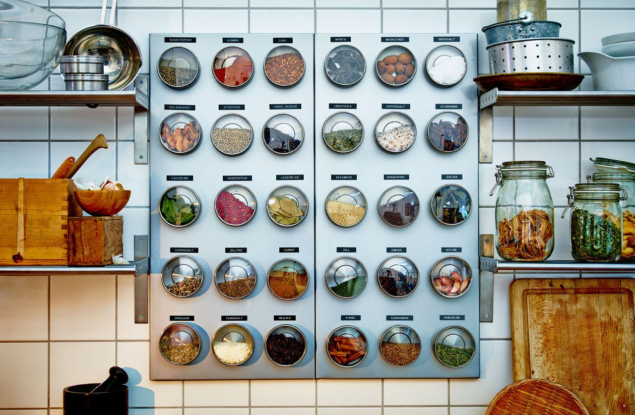 On a white tiled kitchen wall hangs a silver coloured magnetic board ...
