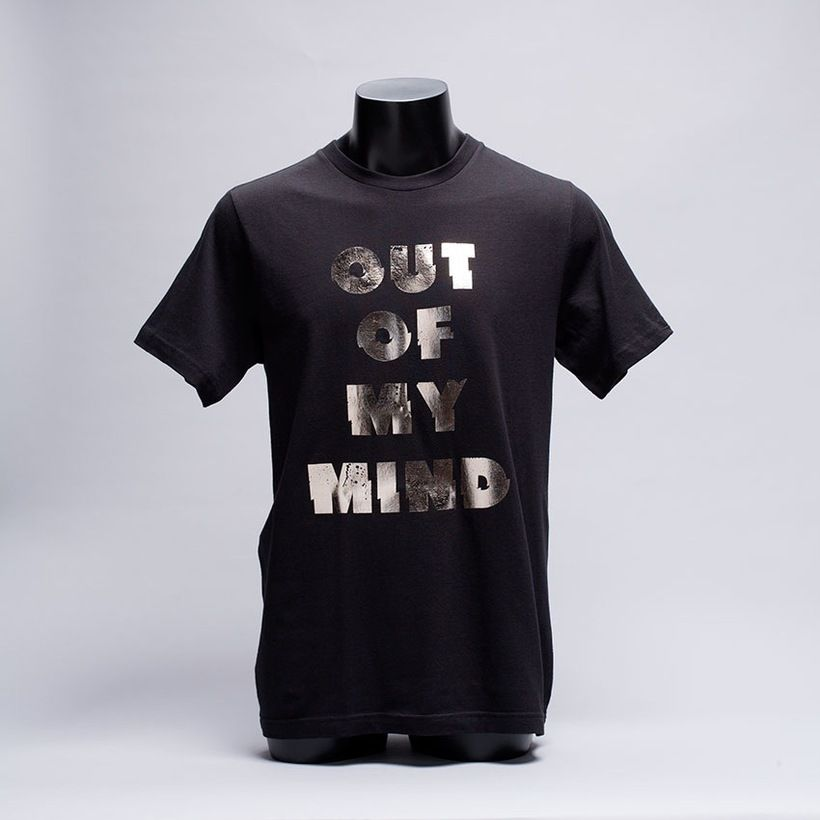 Ultra-soft black cotton tee with Out Of My Mind printed in metallic silver foil on front and custom label on the inside.   4.2 oz. 100% fine ring spun cotton jersey.   Tubular construction with shoulder-to-shoulder tape.   Double needle sleeve and bottom hem.