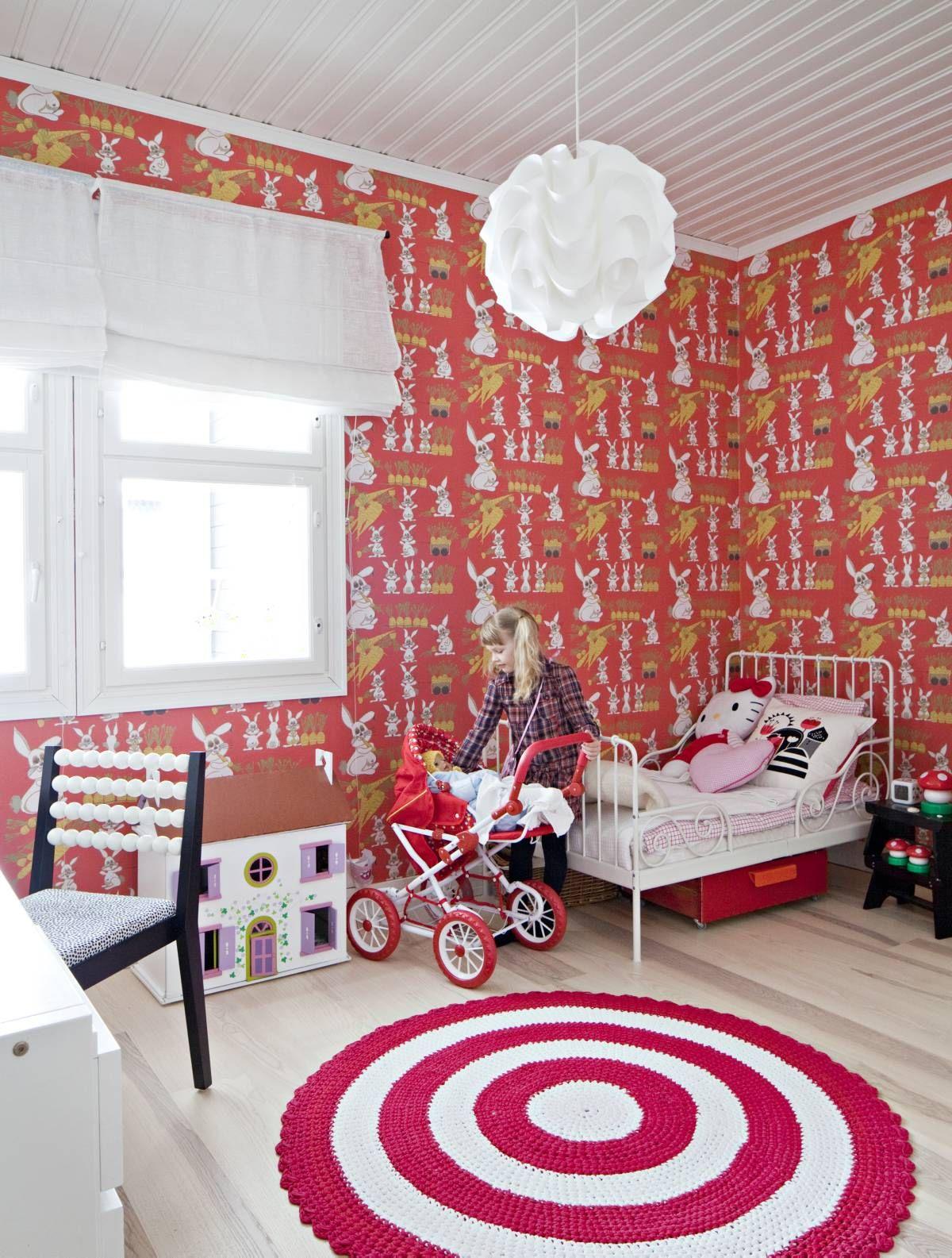 Vilman huoneessa on työpöytä ja vuode sekä säilytystilaa leluille ja vaatteille. Syvänpunainen Jänis istui maassa -pupu-tapetti on Tapettitalosta ja raikkaan näköinen tyynykuosi Darling Clementinen. Hierovalla selkänojalla varustettu tuoli on suunnittelutoimisto Elsan eli Eeva Lithoviuksen ideoima. Riikka-Marin suunnitteleman maton toteutti paikallinen käsityöläinen.