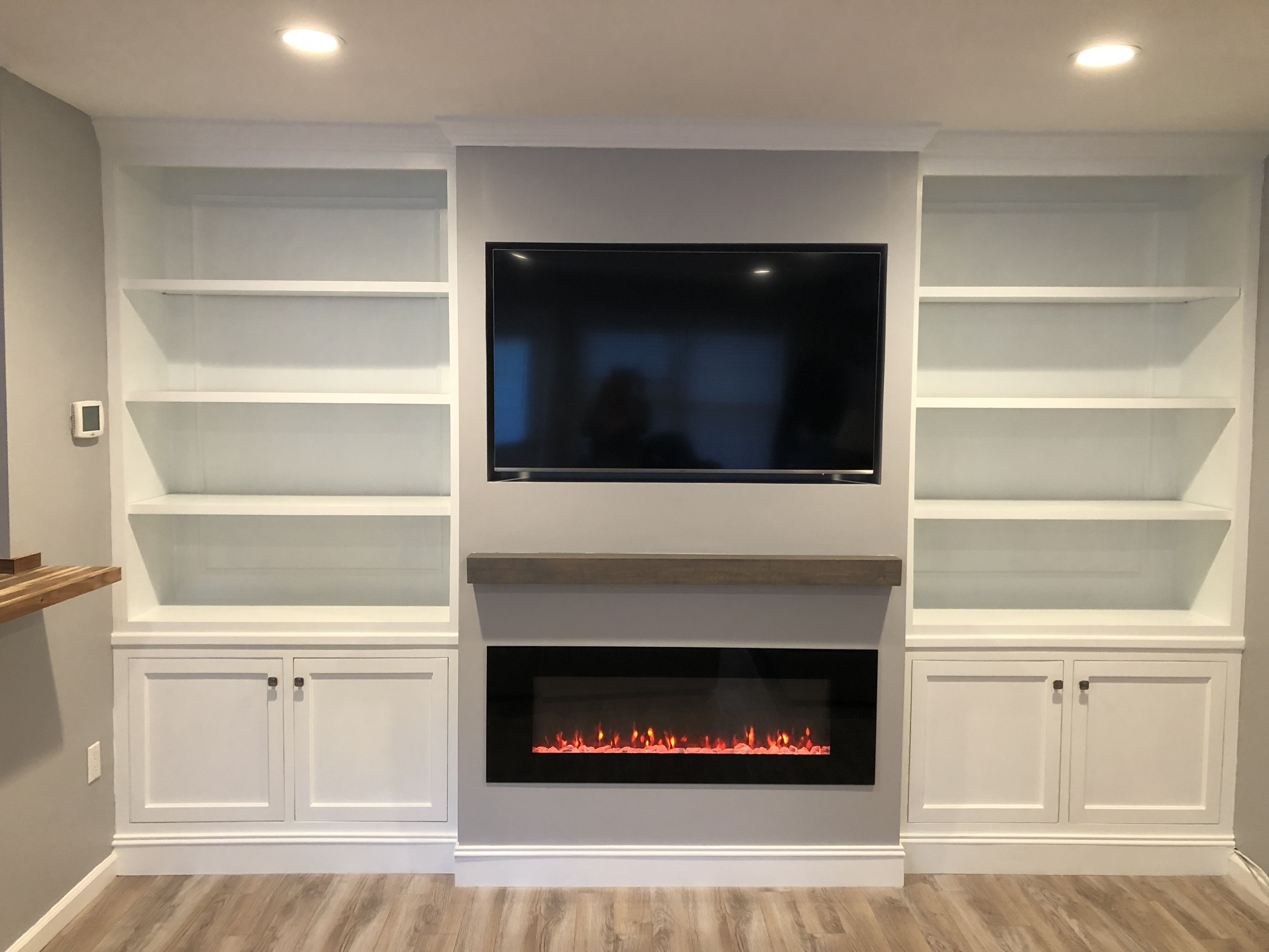 Custom Built In Shelves And Cabinetry With Rustic Mantle Mounted Flat Screen Tv And Modern Electr Linear Fireplace Modern Electric Fireplace Custom Built Ins