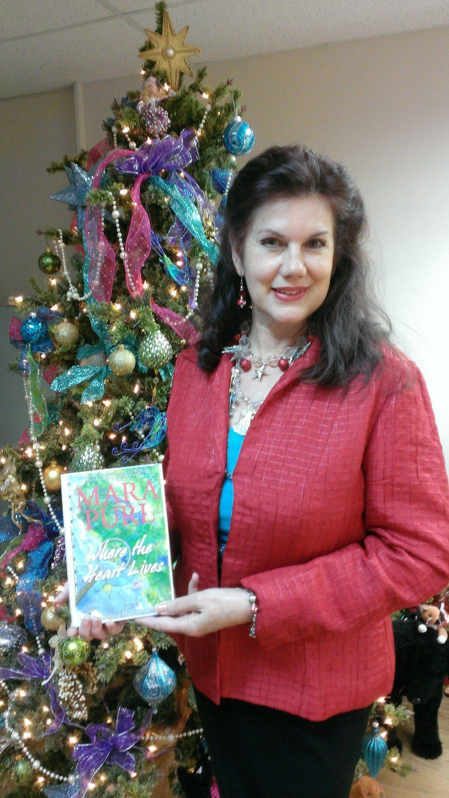 """Holiday Ocean-Book & Jewelry Tea (h) - Mara with """"Where the Heart Lives"""" beside the beautiful All That Glitters Christmas Tree."""