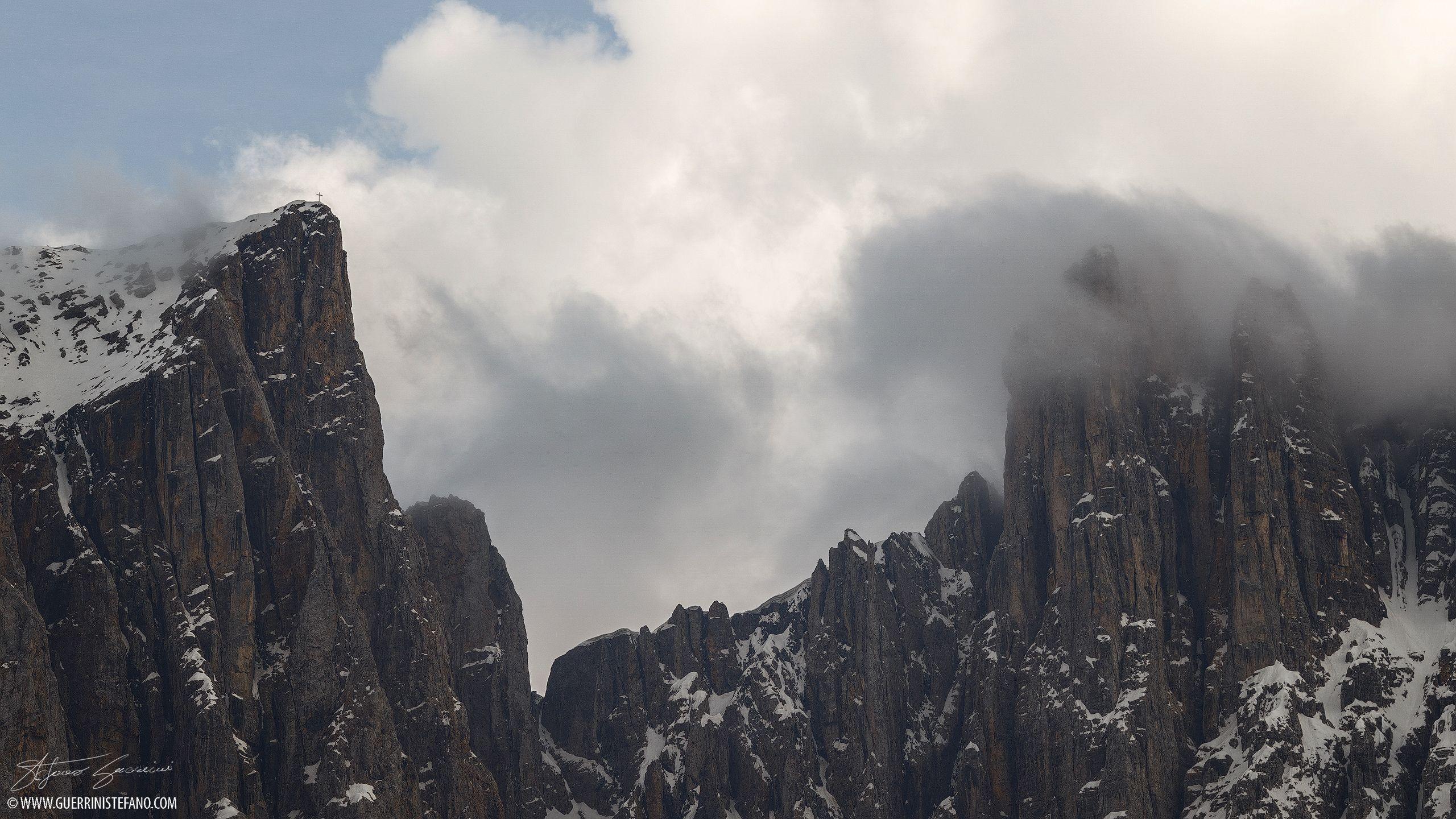 Vista della croce di cima Schenon (2800m) del Latemar, Alto Adige, fra la nebbia, la neve e i colori della roccia. Più a destra la forcella grande del Latemar e la torre Cristomannos avvolta dalle …