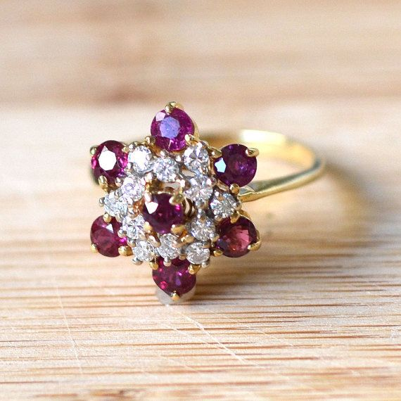 Estate 1.48 carat total weight round ruby and diamond ring. This 14 karat yellow gold ring has 7 round rubies at 1.48 carat total weight and twelve round diamonds at 0.36 carat total weight SI1 clarity H color. Size 7.5.