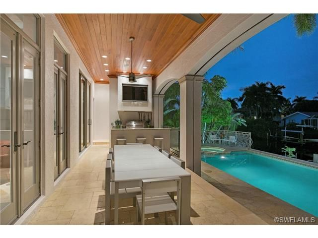 outdoor dining and summer kitchen overlooking the pool wall mounted tv over the grill outdoor on outdoor kitchen tv id=47041