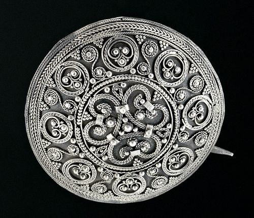 Northern Europe, Viking or Norse culture, ca. 10th century CE. A lavishly decorated domed brooch/pendant comprised of silver (95.7%)sheet, its circular face densely adorned with bands of applied filigree creating a myriad of S-shaped, circular, and curvilinear motifs and further embellished with granulated details. Brooch or pendant.