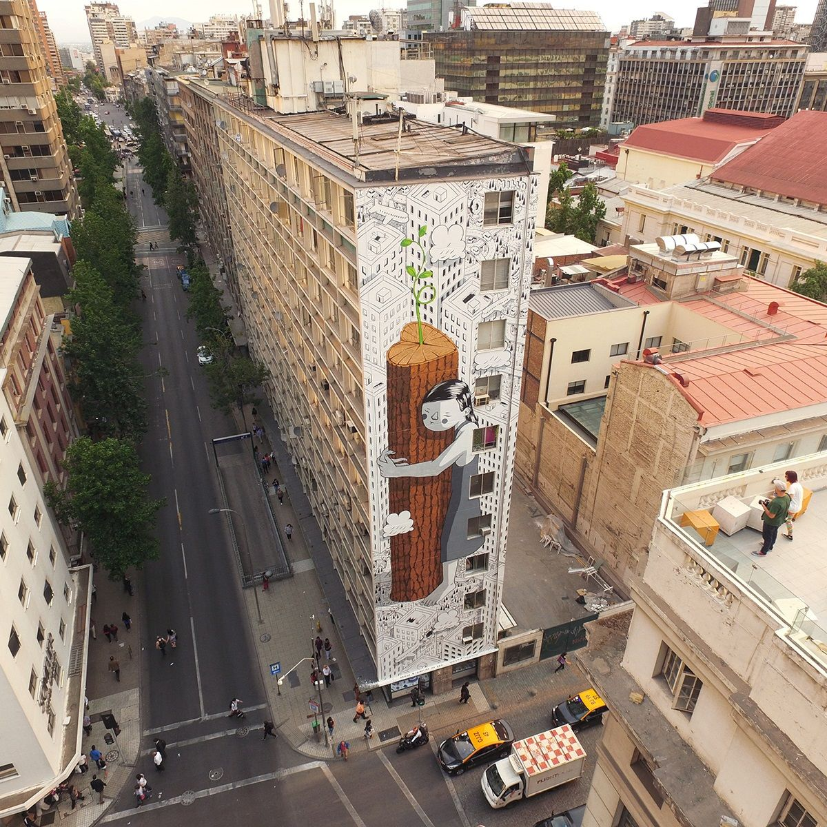 """Painting on the streets of Santiago, Italian artist, Millo once again went big with this super-sized wall which is entitled """"Never Give Up"""". The piece shows some of Millo's signature elements such as the black and white cityscape juxtaposed against a giant little girl which is hugging a heart-shaped tree."""