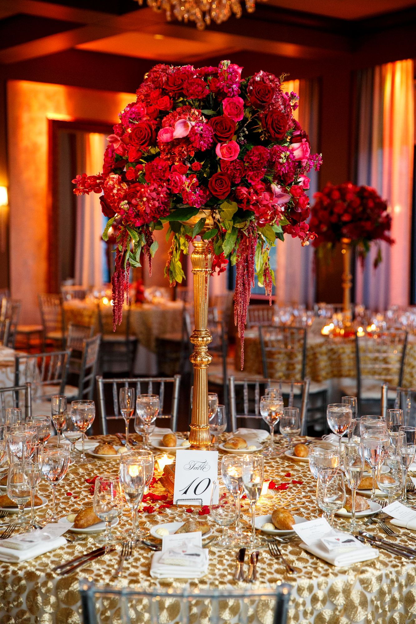 Elaborate red rose centerpiece on gold stand wedding
