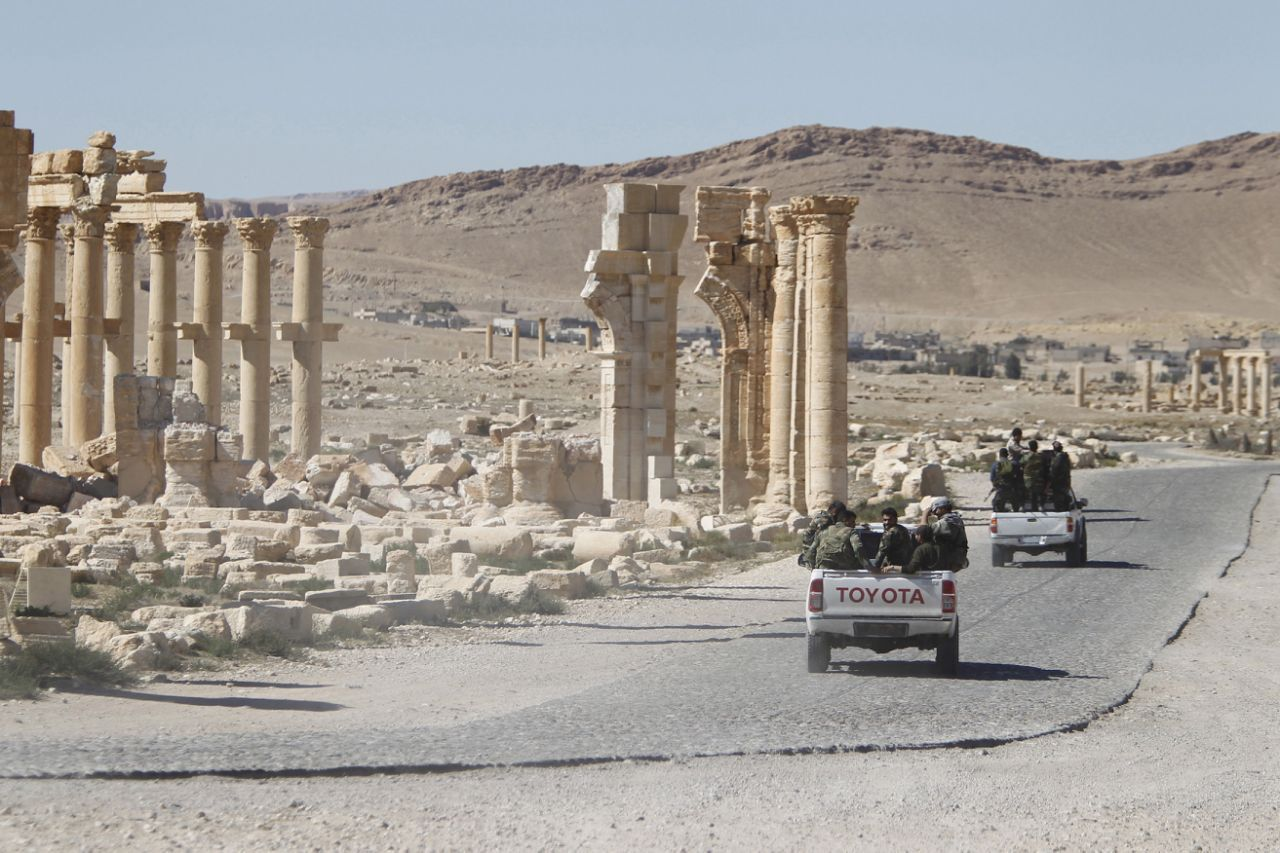 Syrian fighters drive near the ruins in Palmyra.