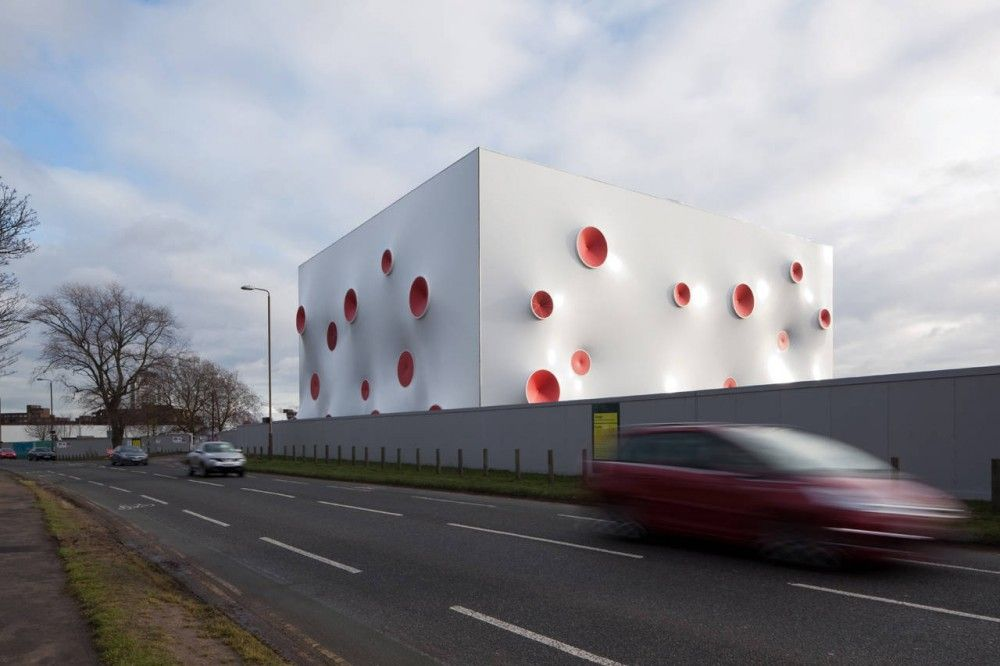 Olympic Shooting Venue by Magma Architecture, London, UK, All three ranges were configured in a crisp, white double curved membrane façade studded with vibrantly colored openings. As well as animating the façade these dots operate as tensioning nodes. The 18.000 m² of phthalate-free pvc membrane functions best in this stretched format as it prevents the façade from flapping in the wind. The double-curvature geometry is a result of the optimal use of the membrane material.