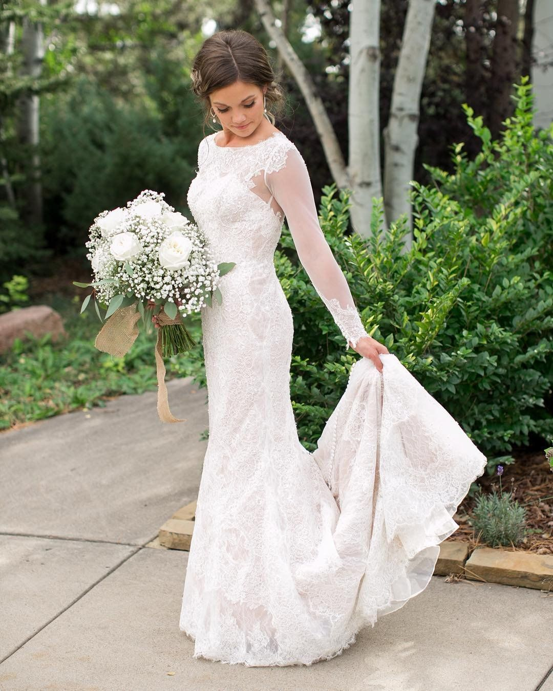 60ca065ecd9 David s Bridal bride Carlee in a long sleeve lace and illusion sheath  wedding dress by Oleg Cassini