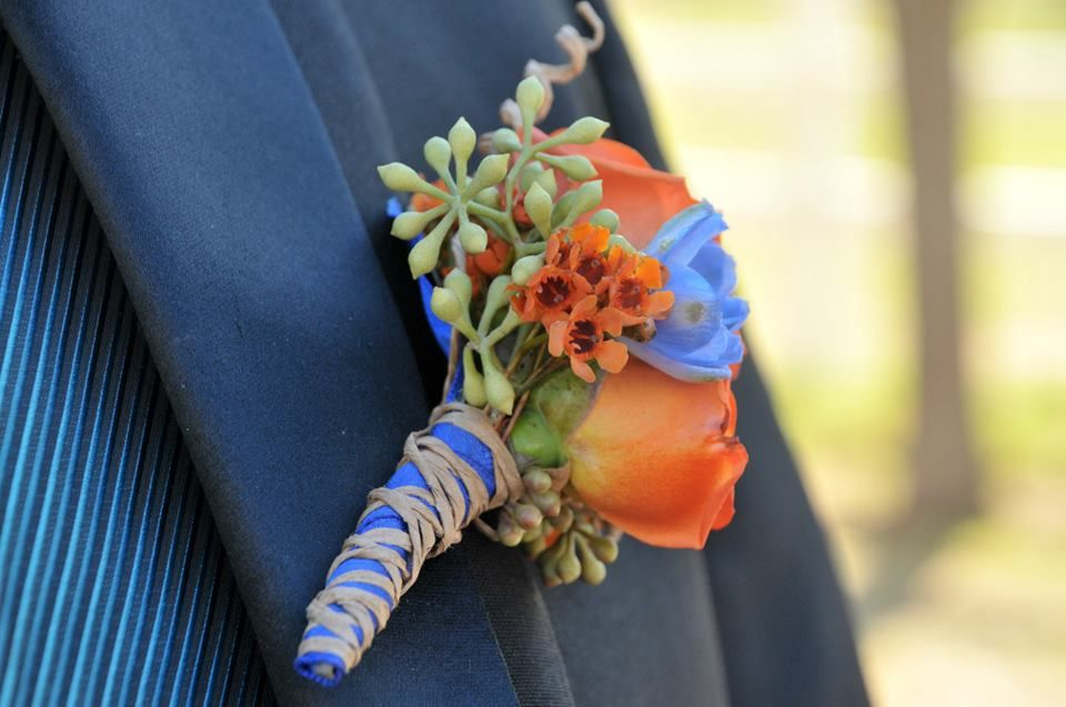 Orange Spray rose and Blue Delphinium Boutonniere with rustic wire for the Groom.