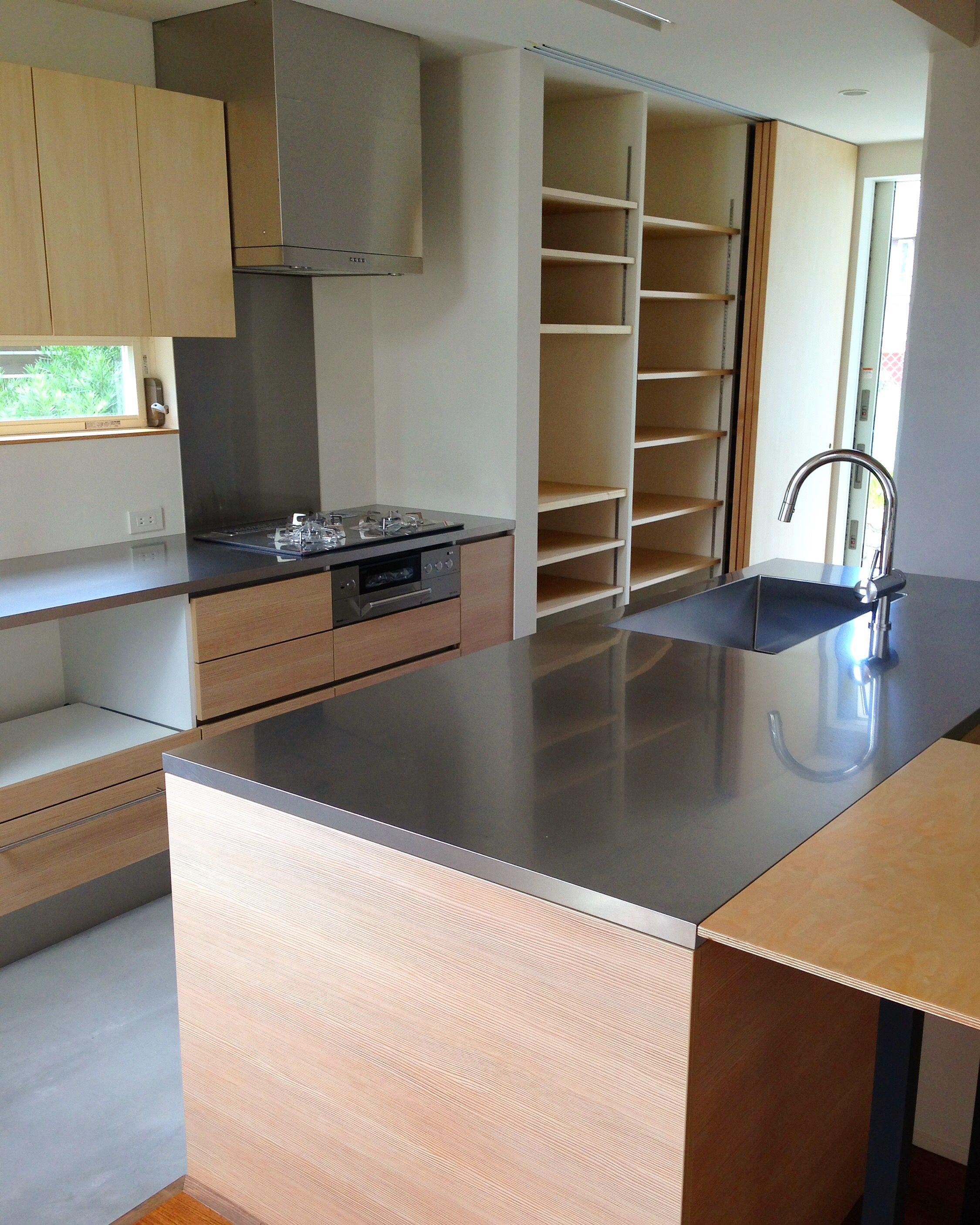 施工事例 型キッチン コンロ前の壁には油汚れや防火のためにキッチンパネルを貼ります このキッチンでは通常のキッチン パネルではなく高級感があるステンレスをキッチンパネルとして使用しています オーダーキッチン 型キッチン リビング キッチン