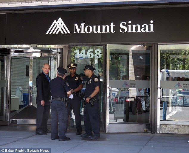 NYPD officers wait outside of the main entrance to Mount