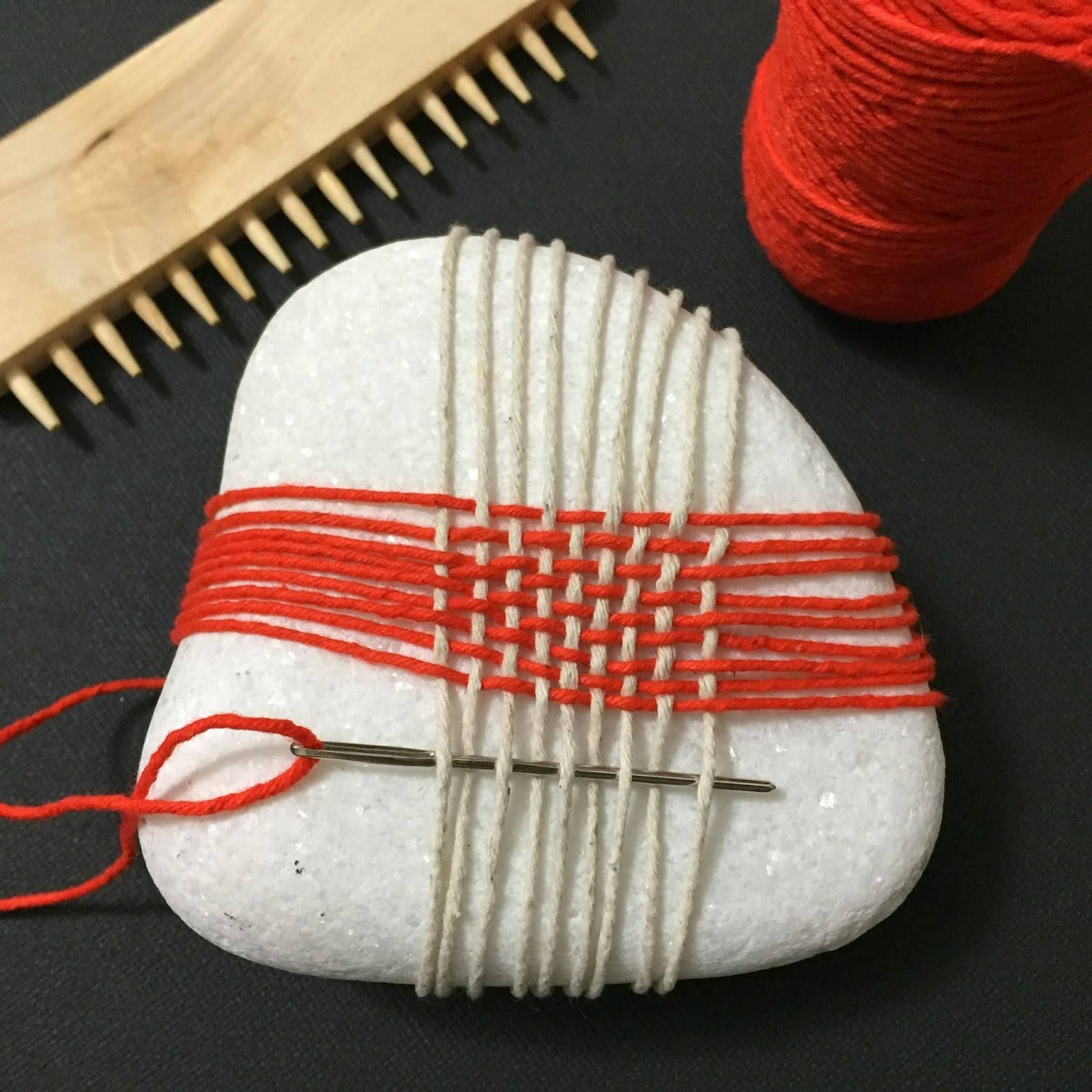 Photo of Using a rock as an loom to create a weaving for the exact same rock!