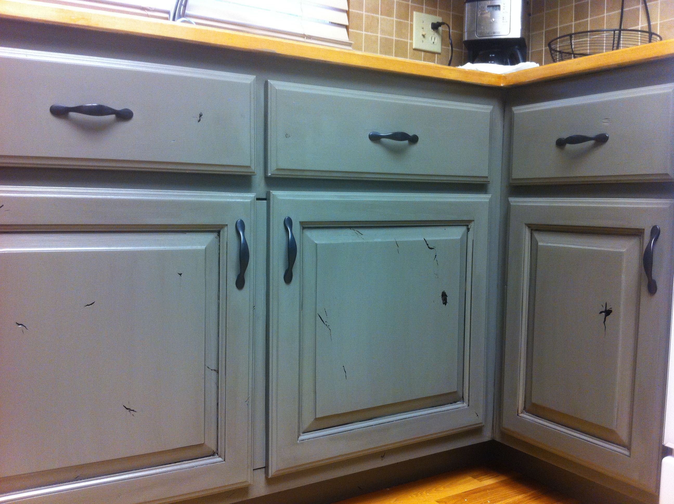 painted knotty alder cabinets with antique glaze lowers are green