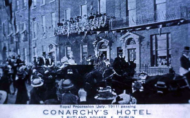 In July 1911 King George V, Queen Mary, with the Prince of Wales and Princess Mary spent six days in Dublin on a royal visit to the city. Thousands lined the streets to view the procession as they drove through Dublin. This image shows the royal party passing Conarchy's Hotel at 7 Rutland Square. Image courtesy of Dublin City Library and Archive.