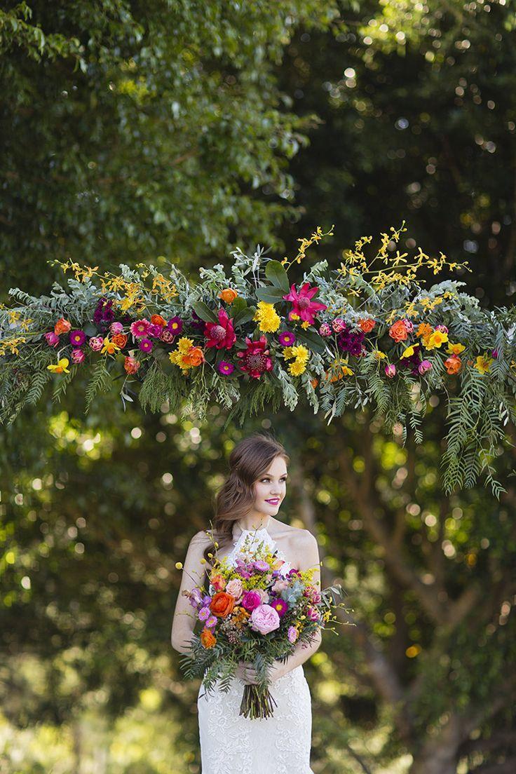 Bright summer wedding ceremony arbour flowers | Lyndal Carmichael Photography