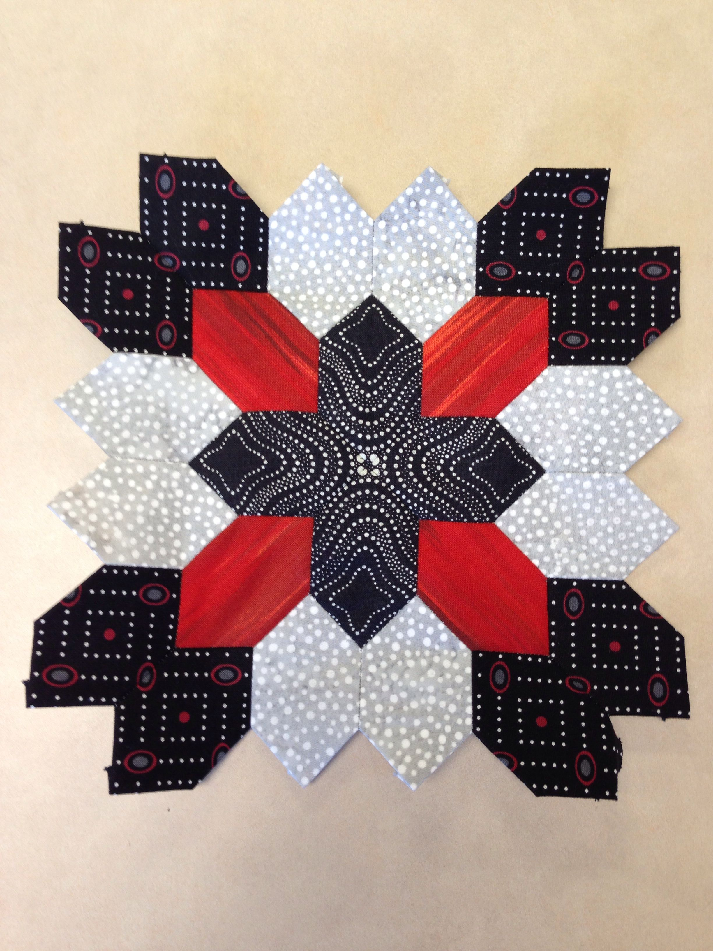 Lucy Boston quilt block made with English paper piecing in black, gray, and red.