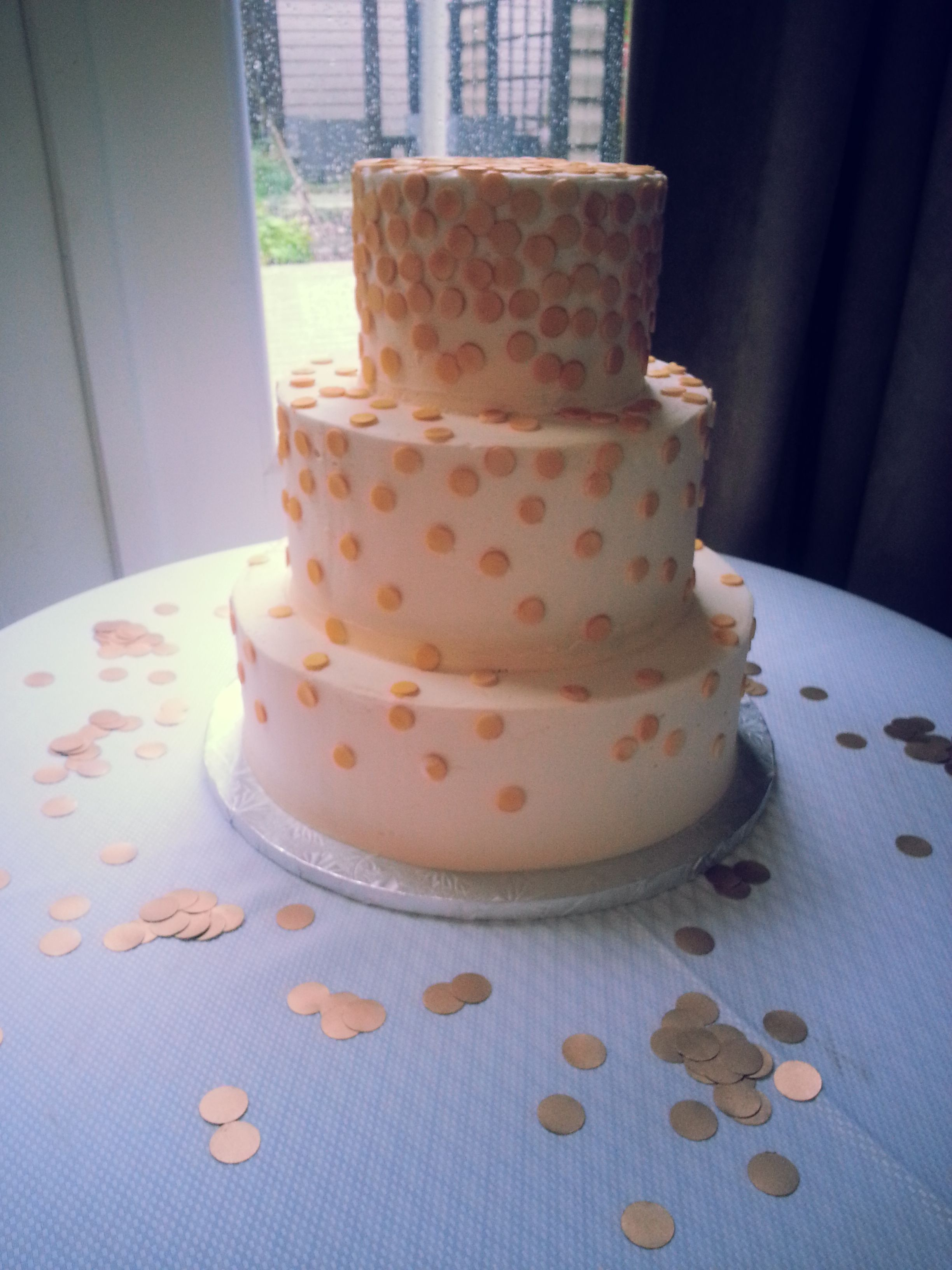 Gold confetti is raining down on this charming wedding cake