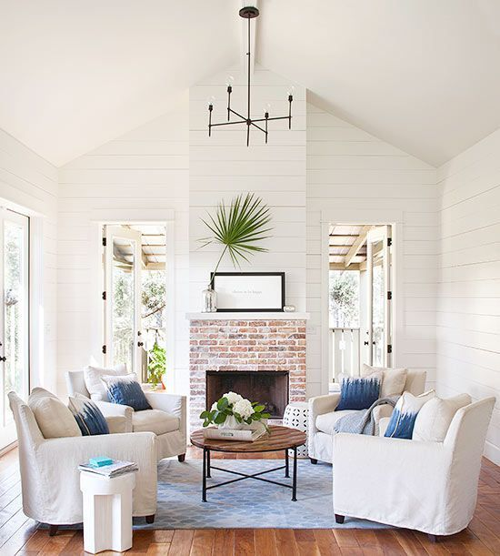Four Matching White Slipcovered Chairs Around A Circular Coffee Table Create The Perfect Conversation Area
